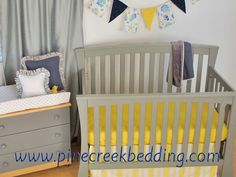 Yellow and grey nursery with navy accents on the blanket, pillow and pennant banner. Banner is a custom made banner with a nautical beach theme fabric.  Banner by Back at the Pond Designs.