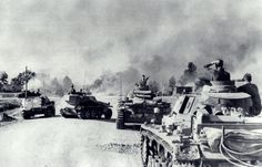 1941 - Spearheading the most forward echelons of the German war machine in Russia is a Panzer Regiment comprising of tanks of II.Abteilung. Halted on the road outside a burning village are two Pz.Kpfw IIIs (tactical number 'II03' and 'III02'), including a 'Befehlswagen', Sd.Kfz. 250 and a Sd.Kfz. 253. A knocked out BT-7 tank can be seen in flames.