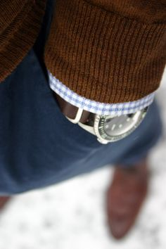 Brown sweater, light blue gingham shirt, navy pants