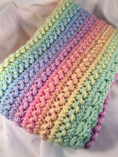Afghan is ready to ship! This crochet baby blanket is bright and colorful and sure to be eye catching. I crocheted this baby afghan with a high quality acrylic yarn in a rainbow of pastel colors. This baby afghan is crocheted in the hairpin lace pattern. Hairpin lace is an old stitch crocheted with a loom to make strips of loops. Those loops are weaved together to make the afghan. It was then trimmed with a mint green broomstick lace border. This afghan is loose and airy which makes it…