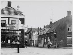 Hoek van de Langenoordstraat en de Brugstraat in Zevenbergen. Op de voorgrond een ANBW wegwijzer.