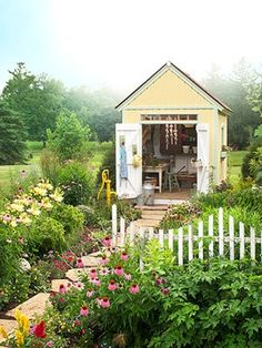 Outside Playhouse with flowers and fence.