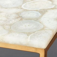Thin, antique brass base defines the clean and simple silhouette of our white agate console table. Cool rectangular top spotlights large white agate pieces, each different in shape/size/tone.