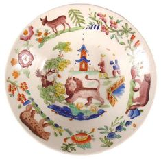 """New Hall Chinoiserie saucer"" Shown is a Chinoiserie pattern on a 5.75 inch saucer that was made by New Hall (1782-1835). It is printed on porcelain with a charmingly naive pattern that includes a large lion among chinamen and pagodas! To see similarly decorated patterns, search ""Chinoiserie / Printed Patterns on Porcelain with Color Added"" in the Pattern and Source Print Database."