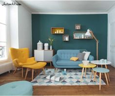 beautiful originality interior of the living room design with blue yellow sectional sofa as well colorful round table as well blue painting wall and glass window behind yellow lounge chair