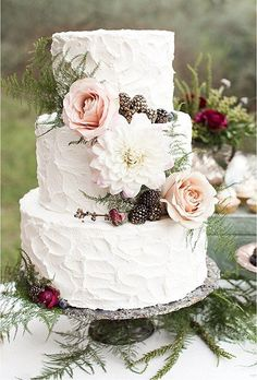 A three-tiered white wedding cake by Elise Cakes with texturized frosting, lush blooms, and rustic pinecones.