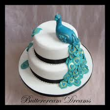 2-layered wedding cake with peacock on side and feathers on the other