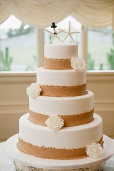 Rustic beach wedding cake with edible burlap trim and starfish cake toppers