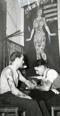 """Shows R.M. Reynolds, a tattoo artist, in his shop drawing a tattoo on the arm of a sailor from the Royal Australian Navy, mural on the wall behind them is of a heavily tattooed woman and bears the inscription """"Alexia, the most beautifully tattooed girl""""."""