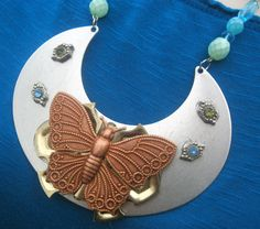 Who knew hinges and butterflies could be so pretty?   This Industrial feel Statement Necklace is layered with a door hinge , discarded metal fabrications, a rose colored butterfly and a touch of sparkle. With the beaded chain this necklace measures approx. 18 inches .