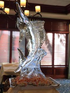 Leaping marlin ice sculpture as the centerpiece for a food display. #icesculptures