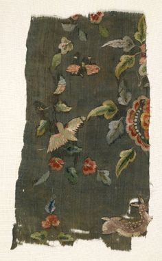Fragment of monochrome plain woven textile made of green silk, embroidered with flowers, leaves, a bird and a deer in coloured silk.