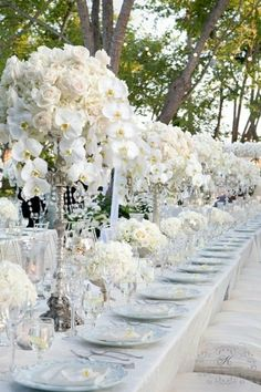 Une longue table de mariage avec des vases hauts et une composition d'orchidées blanches
