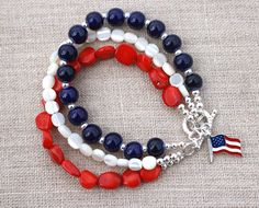Show your support for the USA with this patriotic bracelet. The beautiful red, white, and blue beads are made of coral, ceramic and mother of pearl. The beads are accented with silver plated round beads. Hanging from the silver plated toggle clasp is a silver plated American flag