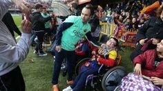 La afición, en el entrenamiento de puertas abiertas, | Andrés Iniesta fotografiándose con aficionados espec iales. | FOTO: MIGUEL RUIZ - FCB