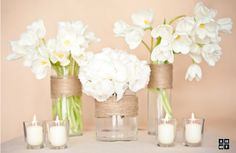 Simple white flowers, twine wrapped vases and tea lights.