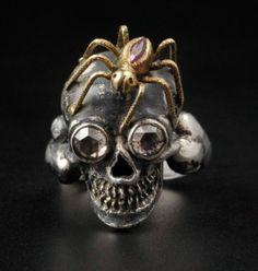 A. Codognato, Venise. Bague en argent noirci, l'anneau stylisant un tibia supportant une tête de mort aux orbites diamantées coiffée d'une araignée en or au corps de rubis. Signé. Poids brut : 10,60 g TDD : 54 VE