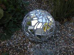 Bowling ball yard art. Bowling ball covered with broken mirrors and grouted.