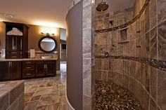 In the home you will find an integrated master suite with a bathroom that includes a curved walk-in shower with pebble tiles, a rain shower and shower jets in the walls as well as a soaker tub nested in a surround of heated tiles and twin vessel sinks set under elegant circular mirrors.  Artez Photography Corp.