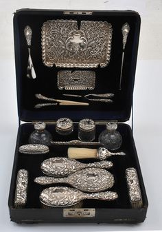 Edwardian sterling silver vanity and dressing set, makers mark Henry Matthews, Birmingham, circa 1901 fashioned in a neoclassical manner with repousse patterns of scrolled shields, masks and partridges within a ground of flora and lattice. The eighteen piece set includes 2 trays, 2 hair brushes and a mirror, 3 clothes brushes, 4 cut crystal jars, a lidded box, a comb, a shoe horn, a button hook, a curling tong and a glove stretcher, housed within the original velvet and satin lined box.