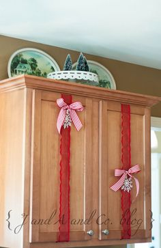 Christmas decor - so simple...don't know why I never thought of this before... Don't love it on the wood but on my white cabinets and my own kind of ribbon & bow this could be a great look for the holidays!