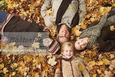 Portrait of Family Lying Down in Autumn Leaves