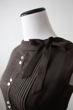 Black pintuck pleated blouse with side neck bow.