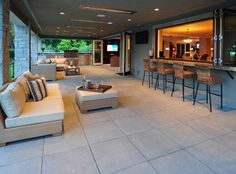 The covered patio, connected to the home via folding doors and windows, features a bar, an outdoor kitchen and inviting seating areas.