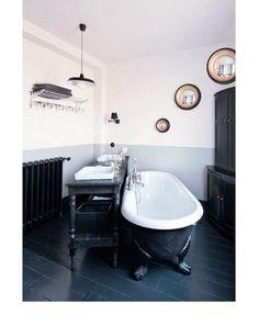 La salle de bain avec sa baignoire à l'ancienne et ses quatre pieds en pattes de lion est plus sobre que le reste de la maison. Les meubles en noir et blanc sont soulignés par un soubassement gris clair.