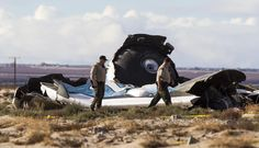 In this Nov 1, 2014 file photo, law enforcement officials take a closer look at the wreckage near the site where a Virgin Galactic space tourism rocket, SpaceShipTwo, exploded and crashed in Mojave, Calif.  (AP Photo/Ringo H.W. Chiu, File)