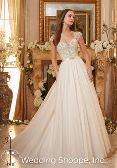 A dreamy and romantic wedding dress with a beaded cap sleeve bodice and tulle skirt.