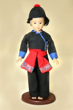This male doll is wearing Green Hmong clothing. The jacket, exposing the stomach, is shorter than those associated with the White Hmong. However, there are groups of White Hmong who wear a similar jacket, especially in Sayaboury Province, Laos. The placket in front goes off to the side, usually on the left. Green Hmong men's pants are baggier than those of the White Hmong, which are cut the same for both men and women. Ideally, Green Hmong men's pants are considered the correct style etc.