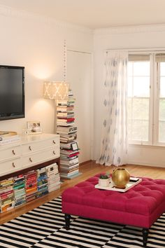 Hot pink square tufted ottoman, black/white rug, print curtains, white sideboard with gold handles