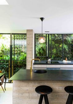 In the kitchen, an exposed concrete island is topped with a steel counter. Darker finishes feature upstairs, where blackened Siberian larch covers the floors and the bedroom walls are painted black.