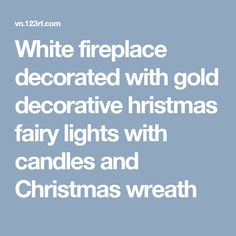 White fireplace decorated with gold decorative hristmas fairy lights with candles and Christmas wreath