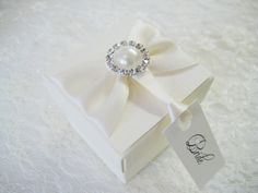 Treat your wedding guests with beautiful personalised favour boxes. These vintage style favour boxes are decorated with ivory ribbon and pearl brooch