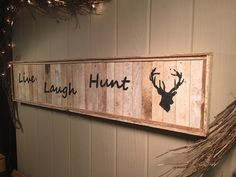 """This rustic wall hanging is made out of reclaimed wood and features stenciled """"Love, Laugh, Hunt and a Dearhead silhouette"""". Its 32"""" by 8""""Due to the differences in the wood being used, each piece has it's own unique character."""