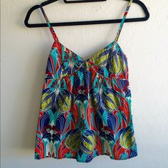 Top shop tree tank Excellent condition, like new. Bold, eye catching colors and beautiful tree pattern! Adorable button detail on backside...see pics 2 & 3. Perfect summer tank...or layered with cami for spring/fall. Versatile...cute with leggings, skinny jeans or maxi skirt. Label says size 2 and it runs small so actually fits like 0. Offers thru offer button  Topshop Tops Tank Tops