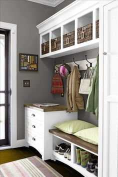 Classic gray and white mudroom with built-in storage shelves and cubbies with wicker baskets, butcher block topped storage bench and cabinet of drawers near the glass paneled front door, coat hooks on the wall, and a tiny abstract oil painting for a dash of color and traditional style.