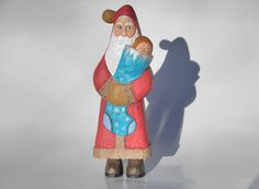 Thank you for viewing my Santa carving.  This offer is for a santa carving I completed in 2011. He is of the Old World style of Santas. I have him holding the stocking left handed instead of to the right. This one is titled, A Dolly for Sue.  About this piece I painted this guy wearing the traditional red robe but with tan fur trim (including the pom-pom on his hat) instead of white and brown boots instead of black jack boots. The stocking he is carrying is painted a turquiose blue with…