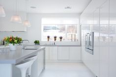 Bright white kitchen has several good pendant. The Romeo Moon S1 Pendant. Designed by Philippe Starck
