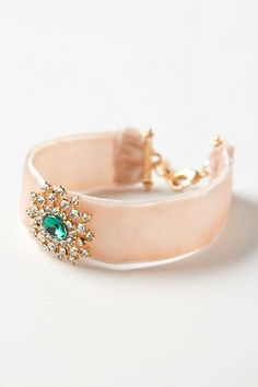 A glittering, aqua gem adorns a simple velvet bracelet, with sparkling rhinestones radiating out of the center like a glimmering sun.