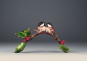 Festive Friends- Two friendly little chickadees have landed amid bright holly leaves and berries, cuddling close to keep each other warm. A solid bronze sculpture by Mark Hopkins 3x5x3 inches