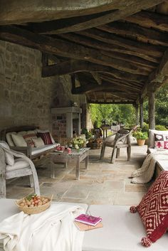 Rustic Porch with exterior stone floors, Rustic throw pillow, Rustic wood furniture, Rustic stone fireplace, Knit blanket