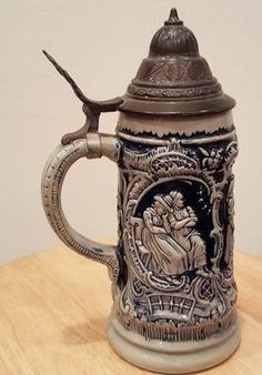 Thewalt Stein Auf Der Alm mold 165. Gray w/cobalt blue and pewter lid (needs cleaning). Lid has nick (see picture), but very much intact. Lid marked DBGM. Stein is 1/2 liter marked 165 at handle. Mode