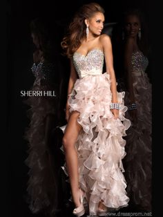 Fresh, playful and fun prom design 21158 by Sherri Hill worthy of a queen. Swing that amazing hi-low skirt featuring tons of fun ruffles cascading dramatically to the floor length. Exquisite iridescent stones take over the curve-hugging bodice which is topped off by a strapless sweetheart neckline and encircled at the high waist by a ribbon belt with sassy bow detail. Find this fun formal gown 2014 in Ivory, Turquoise, Fuchsia, Aqua, Pink, Nude and Light Blue. Perfect to pair with Satin peep…