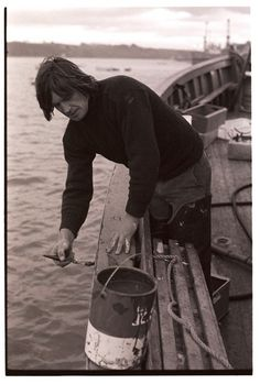 Fisherman painting his boat. Appledore, December 1975. Photograph by James Ravilious © Beaford Arts