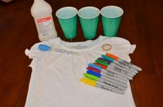 Choose a spot to start and put your cup in right side up and secure a rubber band around the cup rim holding the shirt tightly in place.  Pick your colors and create a small design in the center of the stretched circle. Keep your designs to the size of a quarter or half dollar because the alcohol will make the colors spread out a lot.