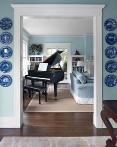"""A Yamaha baby grand piano holds the place of honor. The white skirt on the sofa allows the piece to pop against the rug and echoes the white trim throughout the house. The antique architecture-themed Staffordshire plates were originally displayed in starburst and diamond groupings. Arranging them in a gridlike fashion has turned heads. """"We've had them for a while, but for some reason, people stop and look at them now,"""" David says."""
