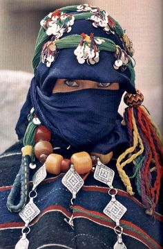 Marriageable young women of the Ait Hadiddou, conceal their reputed beauty under heavy capes and spangled headdresses. The veil places a bride-to-be at a distinct advantage in discreetly surveying the prospects during a three-day festival.  (from article Berber Brides' Fair by Carla Hunt, photo by Nik Wheeler)